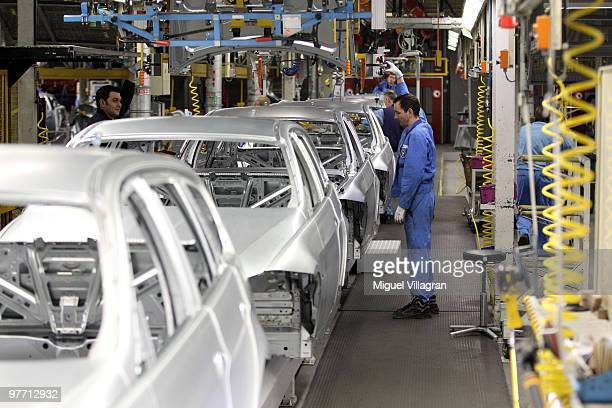 Two workers attach the hood to the car body on the BMW 3series production line at the BMW factory on March 15 2010 in Munich Germany The German car...