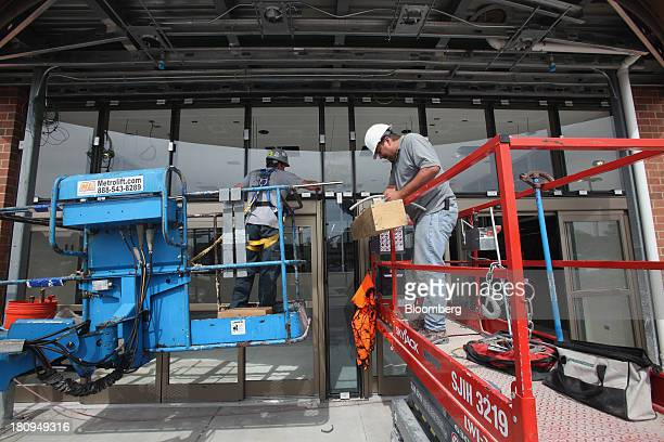 Two workers build the entrance of a new Whole Foods Market Inc. Store under construction in Park Ridge, Illinois, U.S., on Tuesday, Sept. 17, 2013....