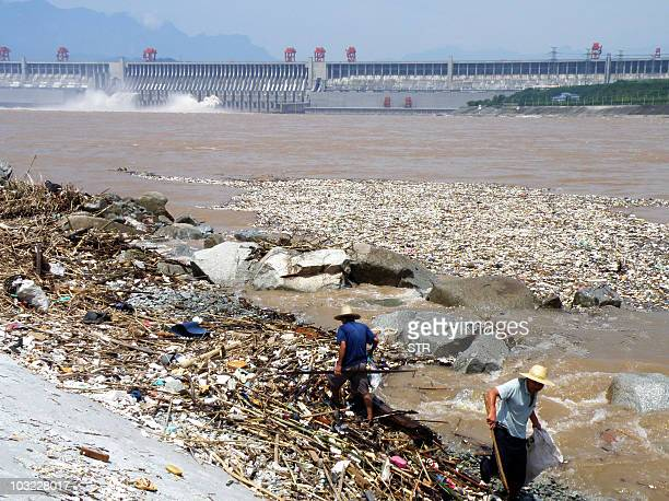 Two workers clean up trash along the bank of the Yangtze River near the Three Gorges Dam in Yichang in central China's Hubei province on August 1...