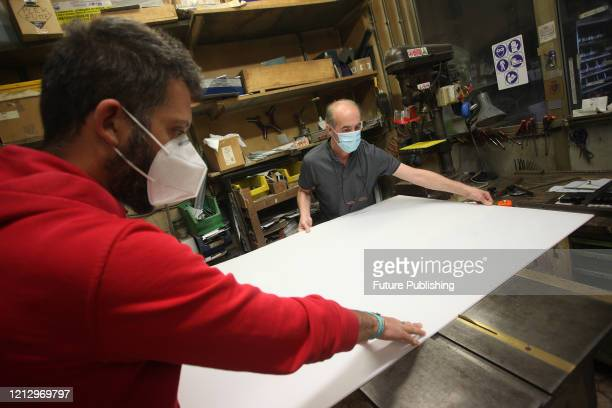 Two workers, during the processing of plexiglass protection panels, a few days after the end of the lookdown to prevent the spread of the...