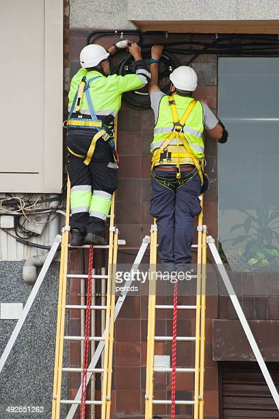 two workers fixing telephone cables. - safety harness stock photos and pictures