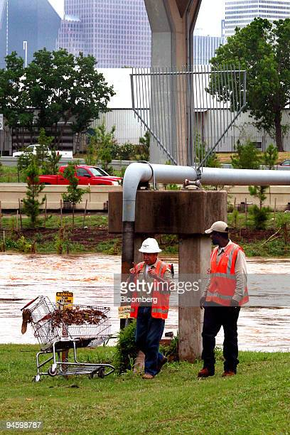 Two workers from CenterPoint Energy check for possible damage to a gas pipeline that crosses White Oak Bayou near downtown Houston Texas Monday June...
