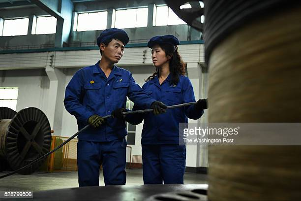 Two workers guide freshly minted cable onto a spooling machine at Pyongyang 326 Electric Wire Factory in Pyongyang North Korea on May 6 2016 Photo by...