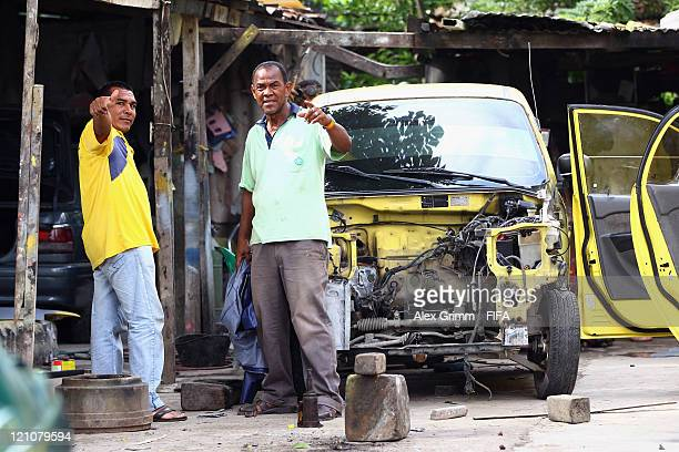 Two workers have a break while repairing taxis at a garage outside Estadio Jaime Moron Leon before the FIFA U20 World Cup 2011 quarter final match...