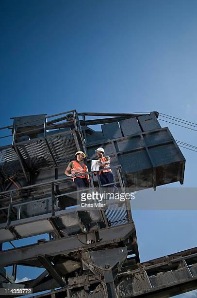 two workers having conversation on excavator