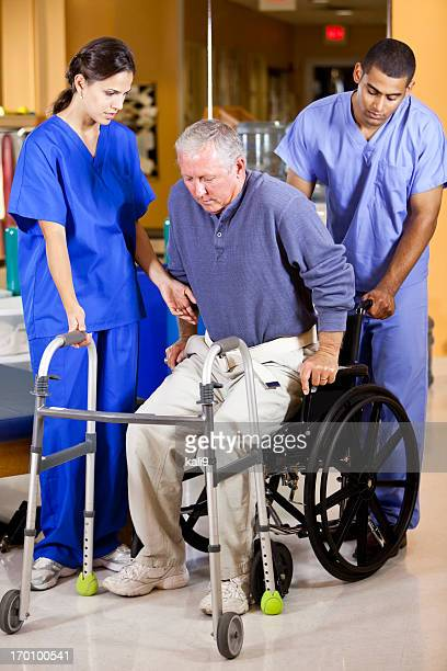 two workers help man out of wheelchair onto walker - african american man helping elderly stock pictures, royalty-free photos & images
