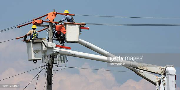 two workers in a crane repairing a power pole - electricity stock pictures, royalty-free photos & images