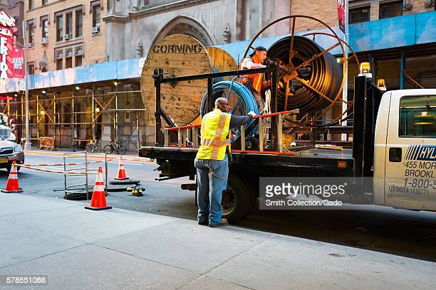Two workers in high visibility vests work to lay fiber optic communications cable on 46th street one block from Times Square in Manhattan New York...
