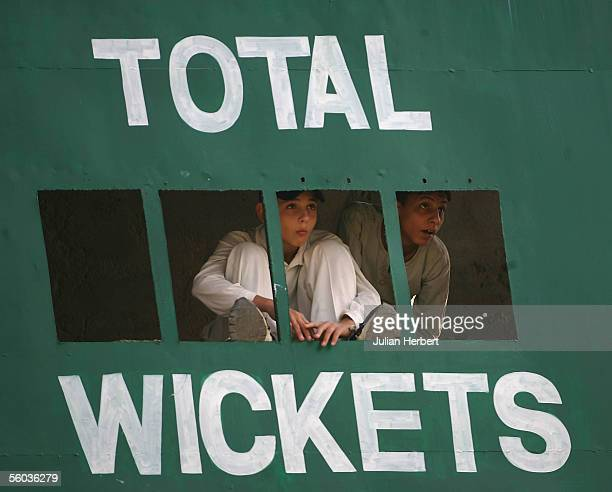 Two workers in the scoreboard watch the first day of a three day game between England and a Pakistan Patrons side on October 31, 2005 in Rawalpindi,...