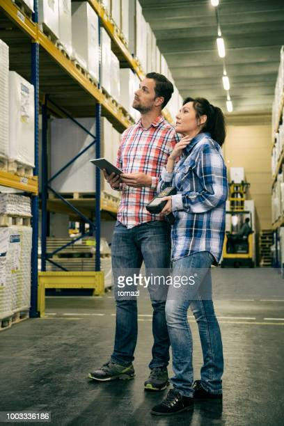 Two workers in warehouse looking at stock