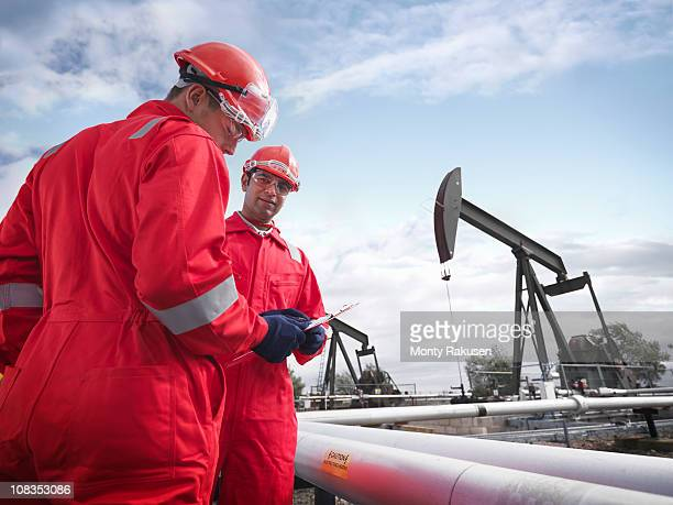 Two workers looking at a clipboard in the foreground with oil pumps above onshore oil wells (nodding donkeys/pumpjacks) in the background