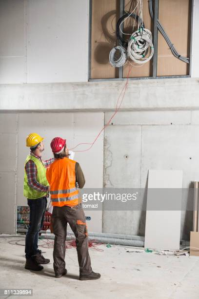 Two workers looking at electric cables