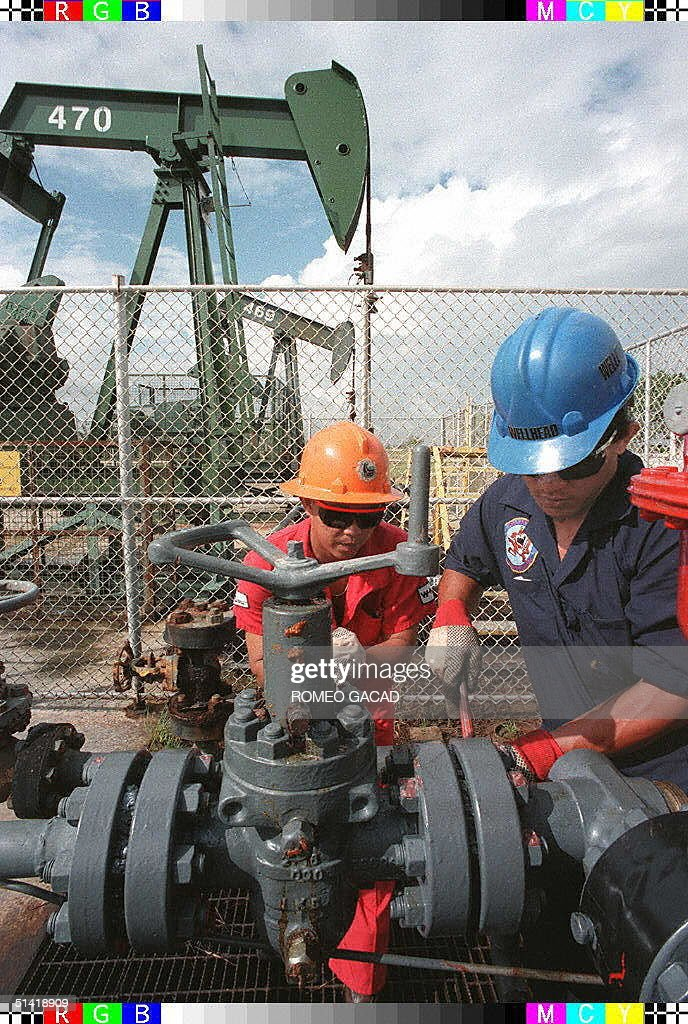 Two workers of the Brunei Shell Petroleum company repair an oil pipe