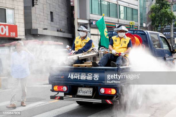 Two workers on a truck spray disinfectant liquid on streets in downtown on June 16, 2020 in Seoul, South Korea.