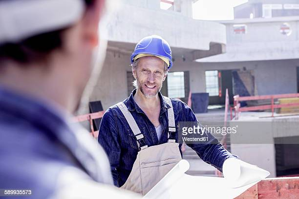 two workers on construction site with construction plan - bauarbeiter stock-fotos und bilder