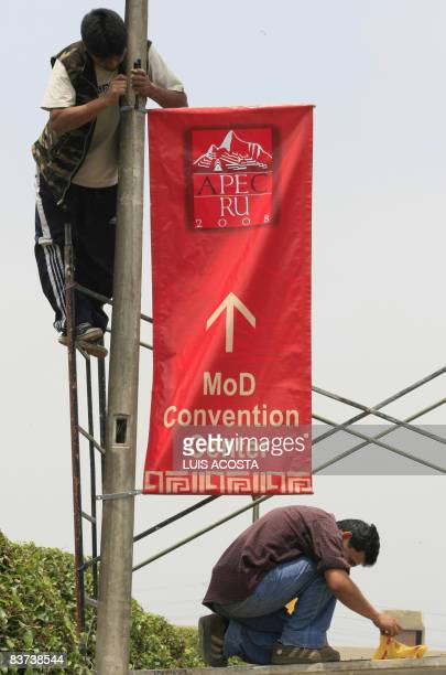 Two workers place a banner on November 18 2008 in the Ministry of Defense in Lima during preparations for the AseanPacific Economic Cooperation...