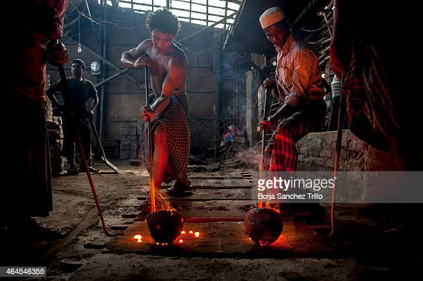 Two workers pour liquified iron into a mold on November 17 2013 in Dhaka Bangladesh Bangladesh currently holds one of the lowest minimum wages in the...