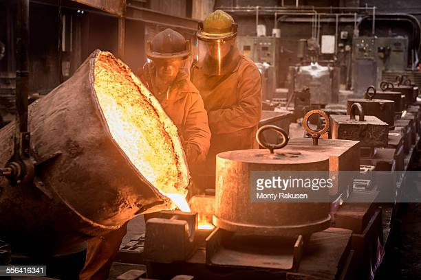 Two workers pouring molten metal from flask in foundry