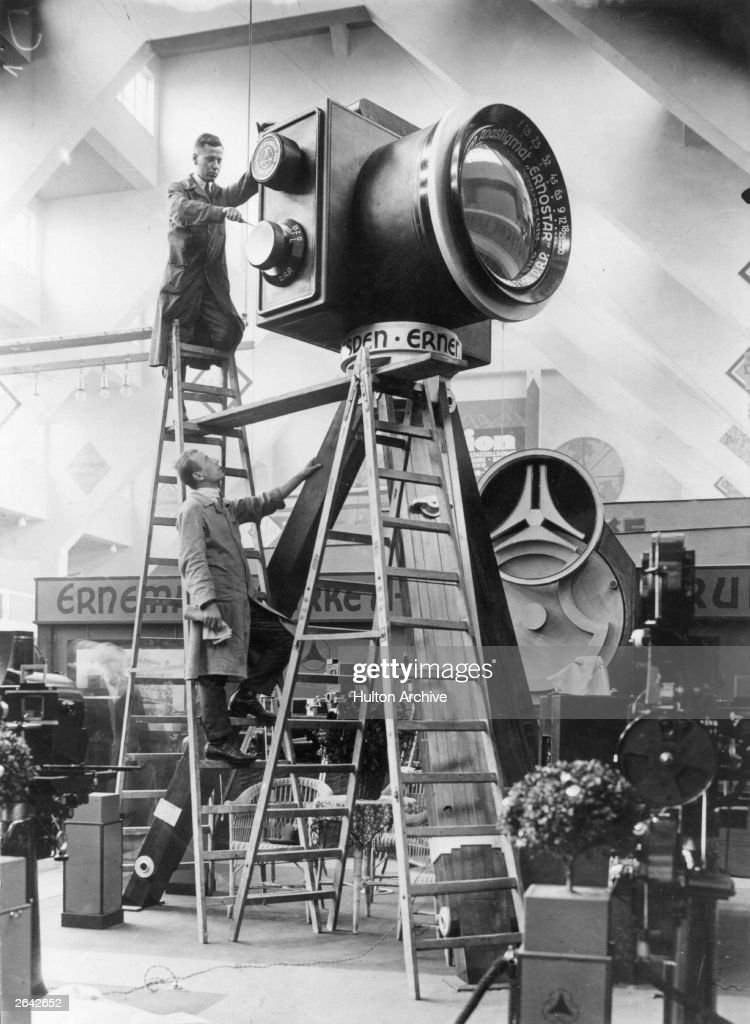 Two workers set up a giant model Erneman camera for the opening of the Kipho Cinema and Photo Exposition in Berlin.