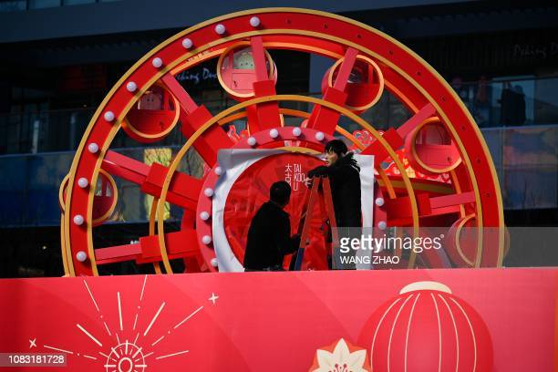 Two workers set up installation outside a store at a business area in Beijing on February 16 2019 China's GDP growth may be significantly slower than...