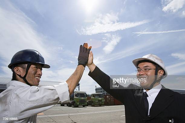 Two workers slapping hands, Side View, Low Angle View