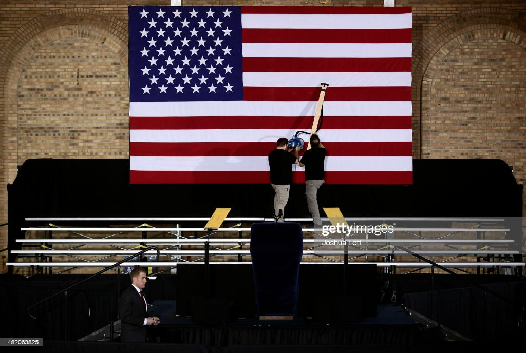 Two workers steam the American flag before U.S. President Barack Obama spoke about his proposal to raise the federal minimum wage at the University of Michigan on April 2, 2014 in Ann Arbor, Michigan. Obama said every American deserves a fair working wage.