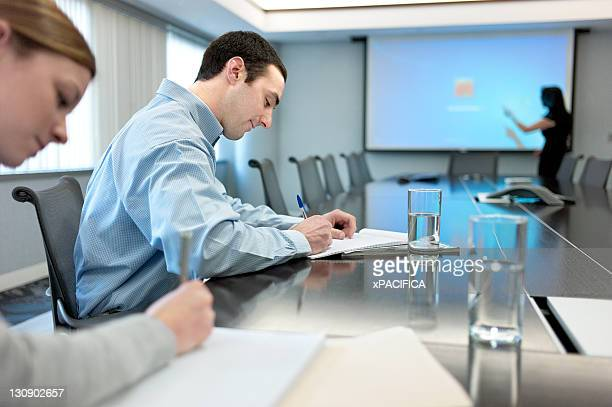 Two workers taking notes during presentation