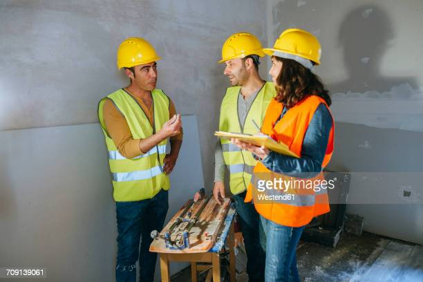 Two workers talking to the boss about money