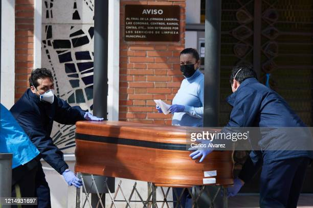 Two workers transport a coffin at La Almudena cemetery on March 26, 2020 in Madrid, Spain. Spain plans to continue its quarantine measures at least...