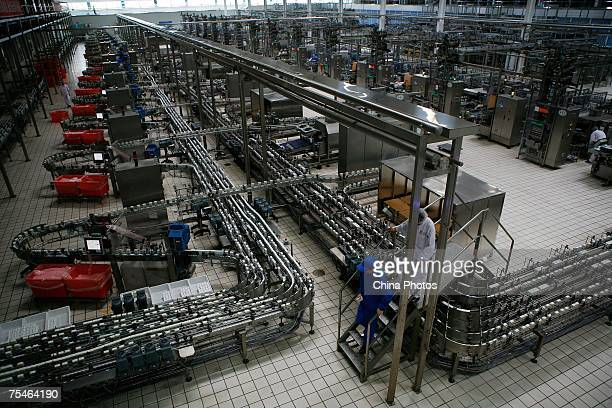 Two workers walk across a liquid milk product line at a plant of Yili Industrial Group Company on July 18 2007 in Huhehot of Inner Mongolia...