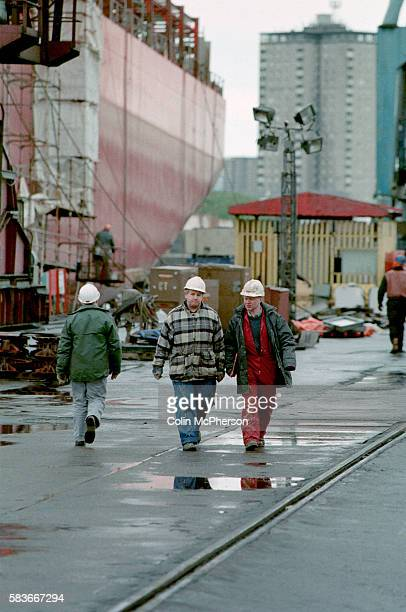 Two workers walking across the yard at the Govan shipyard on the banks of the river Clyde in Glasgow At the time of this photograph the shipyard was...