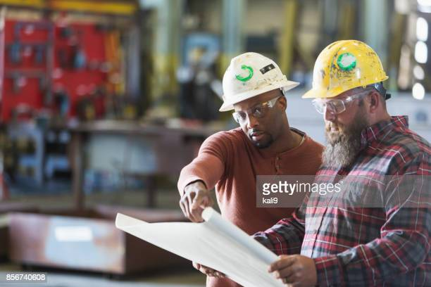 Two workers wearing hardhats looking at plans