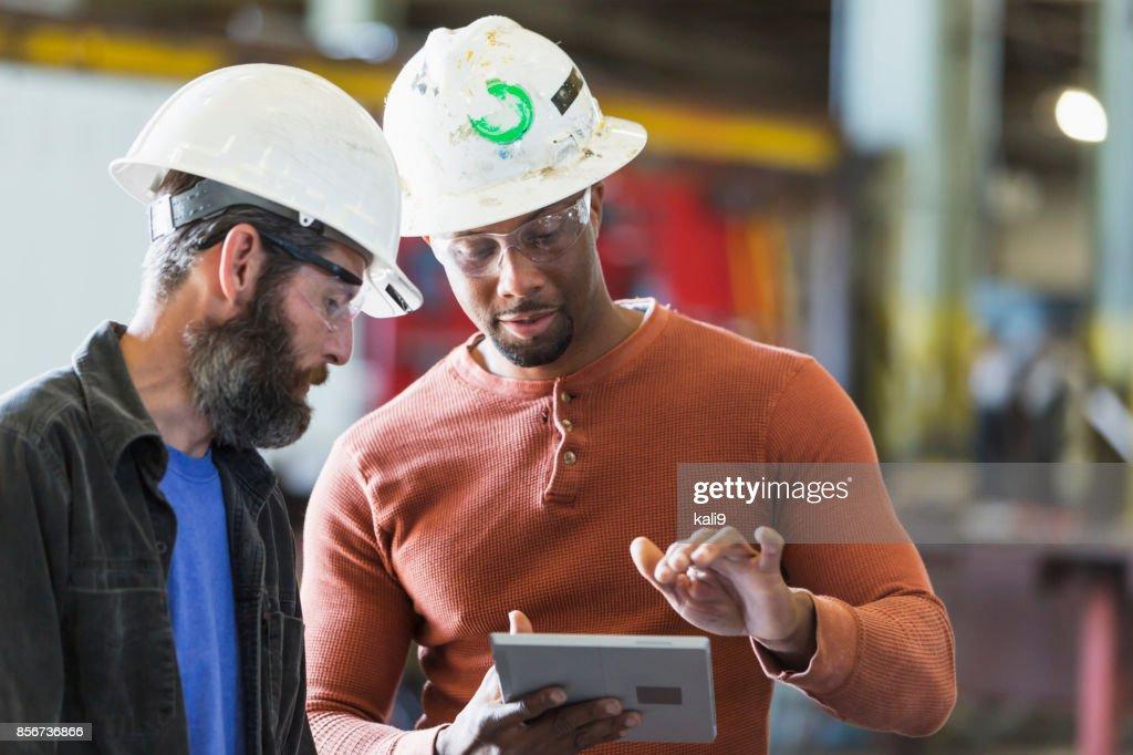 Zwei Arbeiter tragen Schutzhelme mit digital-Tablette : Stock-Foto