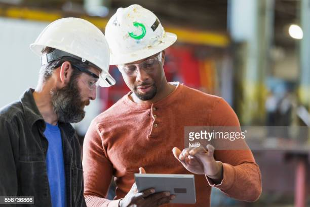 Two workers wearing hardhats using digital tablet
