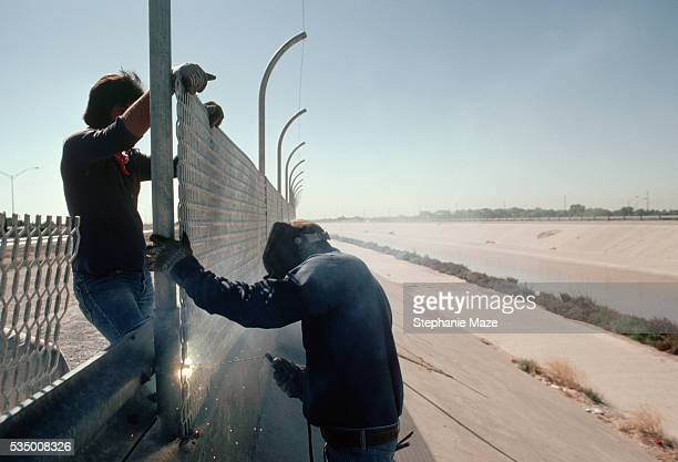Two workers weld part of the galvanized steel fence being built along the length of the border between the United States and Mexico in 1979 The fence...