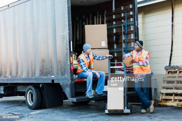Two workers with a truck, moving furniture, boxes
