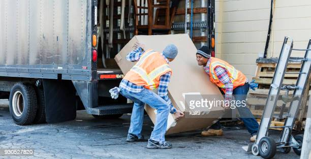 two workers with a truck, moving large box - sollevare foto e immagini stock
