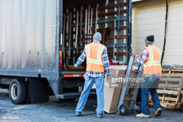 two workers with a truck, moving large box - loading dock stock pictures, royalty-free photos & images