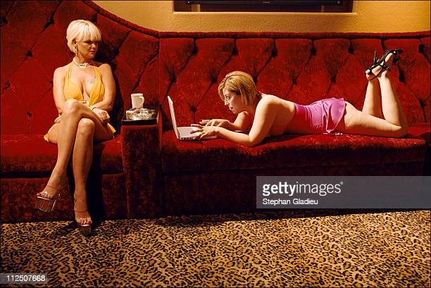 Two working girls killing time while waiting for customers in the parlor of the Moonlite Bunny Ranch a legal brothel owned by Dennis Hof in Lyon...
