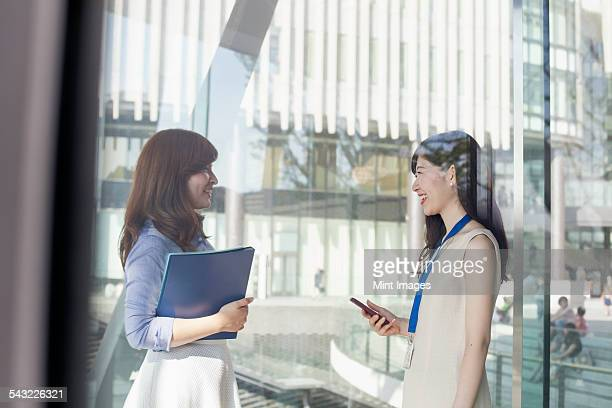 Two working women in an office building.