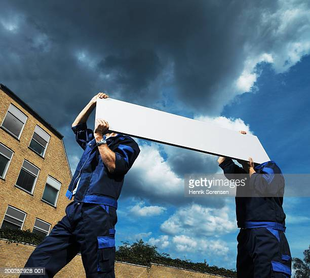 Two workmen carrying plank of wood outdoors, low angle view
