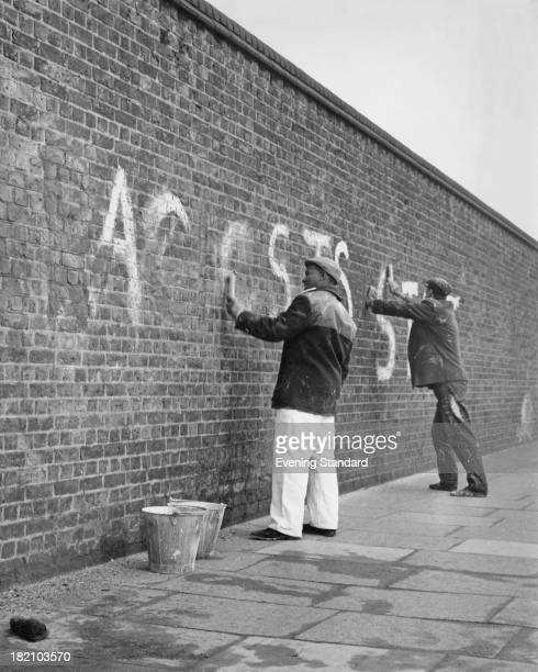 Two workmen clean antiApartheid graffiti from the wall at Lords Cricket Ground London 2nd February 1970