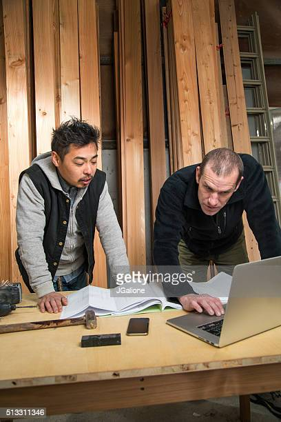 Two workmen discussing something on a computer