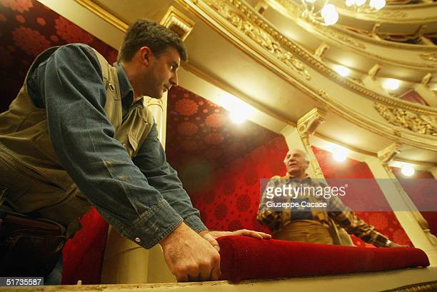 Two workmen fixi a stall inside of the newly renovated Teatro Alla Scala on November 12 2004 in Milan Italy The building the most famous opera...