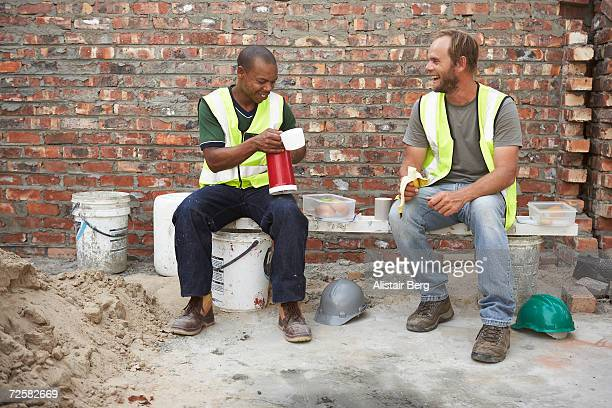 Two workmen on building site enjoying lunch