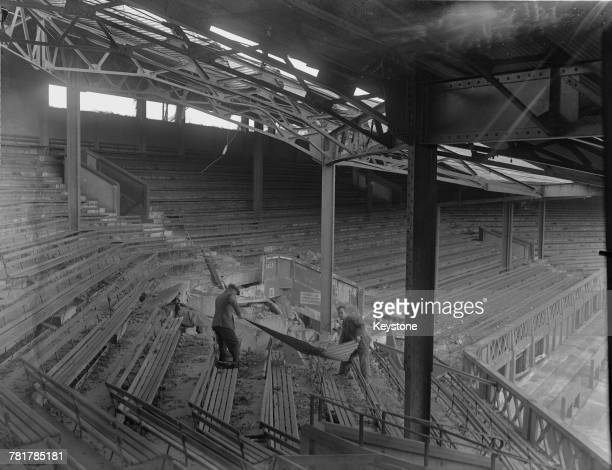 Two workmen remove debris from the blitz bomb damaged south east stand of the Wimbledon Centre Court during the reconstruction on 21 February 1946 at...