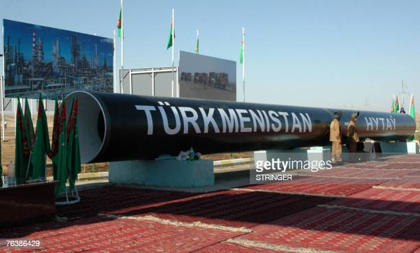 Two workmen stand next to the symbolic first piece of a gas pipeline to China outside of the cityTurkmenabat 30 August 2007 Turkmen President...