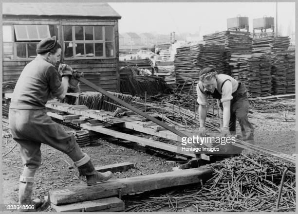 Two workmen using a hand operated machine to cut a 3/8' reinforcing rod during the construction of Coryton Oil Refinery. Coryton Oil Refinery was...
