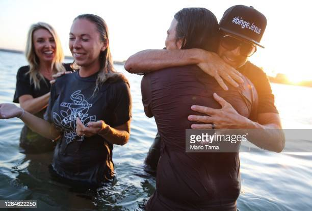 Two worshippers are comforted after being baptized in the Pacific Ocean at the 'Saturate OC' beach revival held amid the COVID-19 pandemic on August...