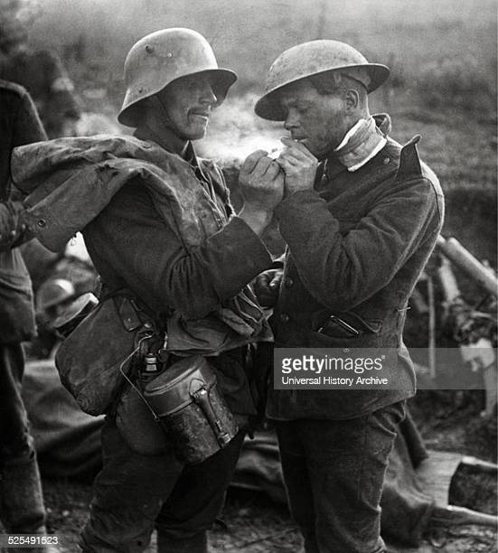 Two wounded soldiers at a British field hospital in France during WW1 A German soldier lights a cigarette for a British soldier 1918
